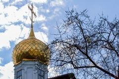 Golden dome and cross of an old church on background of cloudy sky. 2010.04.03, Moscow, Russia. Golden dome and cross of an old church on background of cloudy royalty free stock photography