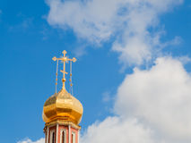 The Golden dome of an Orthodox temple on background of blue sky and clouds. Golden cross on the dome of the temple.  Royalty Free Stock Image