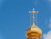 The Golden dome of an Orthodox temple on background of blue sky and clouds. Golden cross on the dome of the temple Royalty Free Stock Photography