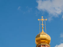 The Golden dome of an Orthodox temple on background of blue sky and clouds. Golden cross on the dome of the temple.  Stock Photos