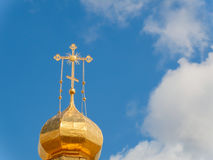 The Golden dome of an Orthodox temple on background of blue sky and clouds. Golden cross on the dome of the temple.  Royalty Free Stock Photography