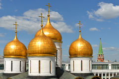 Golden domes of Assumption Cathedral of Moscow Kremlin against blue sky and white clouds Royalty Free Stock Images