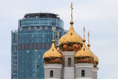 Golden domes of the orthodox church and modern glass building. Golden domes with christian crosses and modern blue skyscraper in background. Religion and stock image