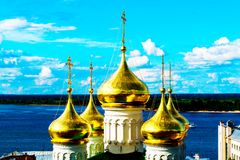 Golden domes of the church near the blue river. A golden domes of the church near the blue river stock photos