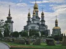 Golden domes of church under the summer blue sky. A graceful path along the campaigns and flowerbeds leads to the church royalty free stock images