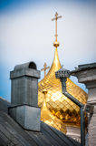 Golden domes with crosses behind old roof. Stock Photos
