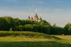 Golden domes with crosses of an orthodox church. Over a green forest royalty free stock photo