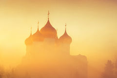 Golden domes in fog in sunlight as background. Winter frosty misty morning Royalty Free Stock Photo