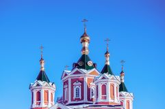 Golden domes with golden crosses over a monastery in Russia against a blue clear sky.  royalty free stock image