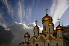 Golden Domes at the Kremlin, Moscow, Russia. A dazzling spray of clouds backs the shimmering golden onion domes of a cathedral on the grounds of the Kremlin in Stock Photos