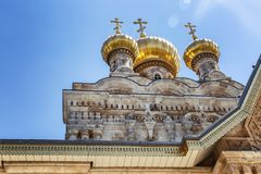 Golden domes of an old orthodox temple on a background of bright blue sky. Horizontal stock photography
