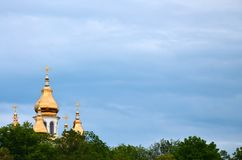 Golden domes of an orthodox church among blossoming trees agains. T a background of a cloudy blue sky royalty free stock images