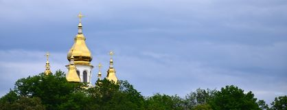 Golden domes of an orthodox church among blossoming trees agains. T a background of a cloudy blue sky stock photography