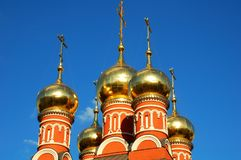 Golden domes with Orthodox crosses on the background of blue sky on the Church of St. Nicholas on the Chips, Moscow, Russia. Close-up. Horizontal view Royalty Free Stock Photo