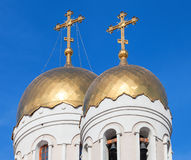Golden domes of Russian orthodox church with cross against blue Royalty Free Stock Photo
