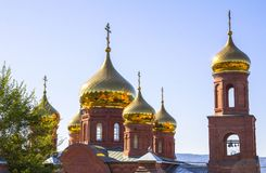 Golden domes of the temple against the blue clear sky. Christianity, religion. Friary stock photo