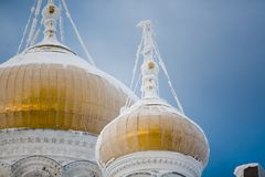 Golden domes. The golden domes of the white Russian monastery, which are covered with snow and ice royalty free stock photo