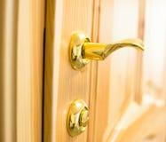 Golden door handle and lock on the wooden door Royalty Free Stock Photography