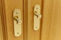 Golden door knobs detail on an oak wooden door. Horizontal Royalty Free Stock Photography