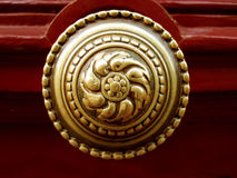 Golden door knocker. Old golden door knocker on red door royalty free stock images