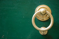Golden door knocker copy space. Old elegant golden metal door handle, knocker Stock Images
