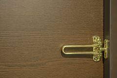 Golden door latch and wood grain background royalty free stock photography