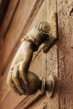 Golden doorknocker with hand shape on old wooden door. Golden doorknocker with hand shape on old brown wooden door in Alcaraz, Albacete, Spain Royalty Free Stock Image