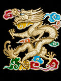 Golden dragon with colorful clouds black backgroun Royalty Free Stock Photos