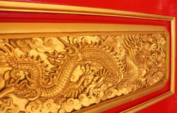 Golden dragon decorated on red wood wall Royalty Free Stock Photos