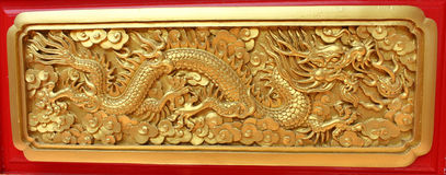 Golden dragon decorated on red wood wall Stock Photos