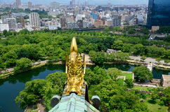 Golden dragon fish statue or Shachihoko at roof top and aerial v. Iew around Osaka castle from atop of Osaka Castle on July 10, 2015 in Osaka, Japan Stock Photos