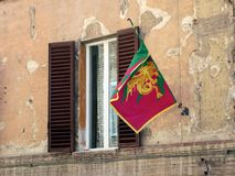 Golden Dragon Flag, Siena, Tuscany, Italy. Sienna contrade gold dragon flag, mounted on traditional Italian stucco building with wooden shutters, Siena, Tuscany Royalty Free Stock Photography