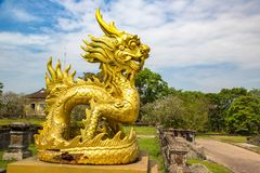 Golden dragon in Hue, Vietnam. Golden dragon statue located inside Imperial Royal Palace, Forbidden city in Hue, Vietnam in a summer day royalty free stock photo