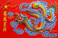 A golden dragon in red wall. A chinese golden dragon at red wall in chinese temple , Pattaya Thailand Stock Photography