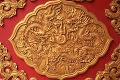 Golden dragon sculpture decorated on red wall Royalty Free Stock Images