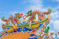Golden dragon statue on public shrine roof, Thailand, Dragon prominently. In the beautiful on blue sky background stock photography