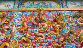 The golden dragon statue on wall Royalty Free Stock Images