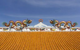 Golden dragons on the roof. Twin golden dragons Statue on the roof of Chinese temple Stock Images