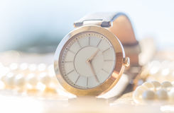 Golden dream. Golden wrist watch, golden woman watch concept with white pearls Stock Photography