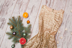 Golden dress with sequins on a wooden background, spruce branch and balls and citrus Royalty Free Stock Photography