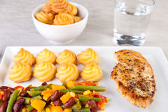 Golden duchess potatoes with grilled chicken and mexican vegetables Royalty Free Stock Photography