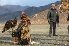 Golden Eagle Hunter came to took the prey from the bird, stroked it, gave her a piece of meat, in desert mountain of Western Mongo Royalty Free Stock Image