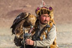 Golden Eagle Hunter, while hunting to the hare holding a golden eagles on his arms. SAGSAY, MONGOLIA - SEP 28, 2017: Golden Eagle Hunter, while hunting to the Stock Photos