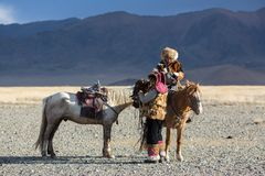 Golden Eagle Hunter teaches her young daughter hunting with birds of prey to the hare in desert mountain of Western Mongolia. SAGSAY, MONGOLIA - SEP 28, 2017 Stock Image