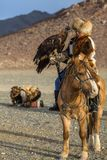 Golden Eagle Hunter teaches her young daughter hunting with birds of prey to the hare in desert mountain of Western Mongolia. SAGSAY, MONGOLIA - SEP 28, 2017 Stock Photo