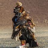 Golden Eagle Hunter teaches her young daughter hunting with birds of prey to the hare. SAGSAY, MONGOLIA - SEP 28, 2017: Golden Eagle Hunter teaches her young Stock Photo
