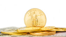 Golden eagle standing on edge. One ounce of golden eagle standing on edge on other golden coins royalty free stock photo