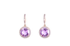 Golden earings with amethysts. Golden earings with round-shape lilac gems isolated on the white background Stock Image