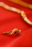 Golden earrings and chain on red silk Royalty Free Stock Images