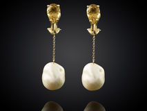 Golden earrings with pearl isolated on black background Royalty Free Stock Photo